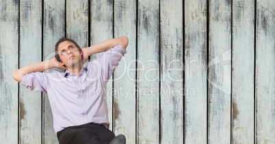 Thoughtful businessman sitting with hands behind head against wooden wall