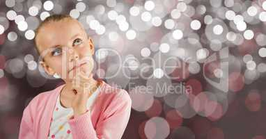 Thoughtful girl with hand on chin over bokeh