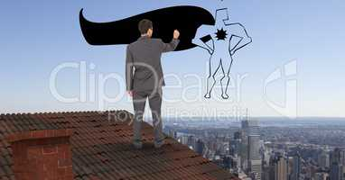 Rear view of businessman on roof drawing super hero in midair