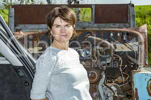 Woman stands in front of old scrap car
