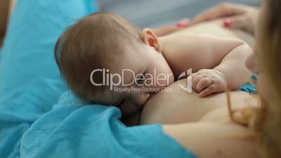 Adorable newborn baby being breastfed by mother