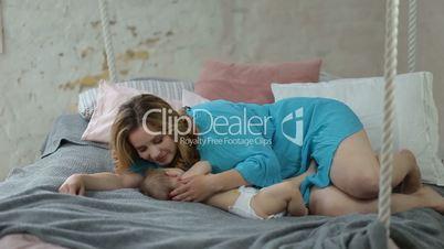 Beautiful mom kissing her sleeping baby girl