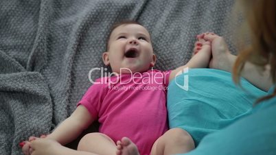 Laughing infant child getting massage by mother