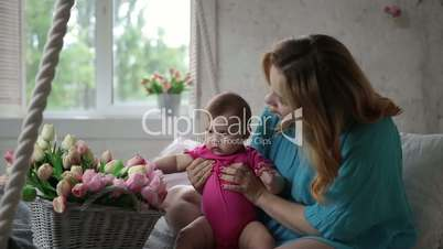 Adorable baby girl playing with tulip flowers