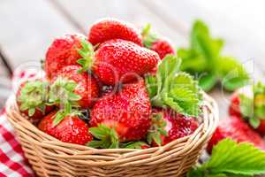Fresh strawberry in basket on wooden rustic table, closeup. Delicious, juicy, red  berries. Healthy eating.