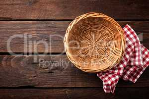 Empty wicker basket on a wooden background, top view