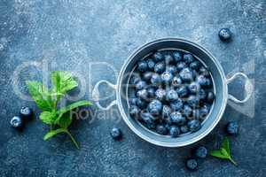 Fresh Blueberries in a bowl on dark background, top view. Juicy wild forest berries, bilberries. Healthy eating or nutrition.