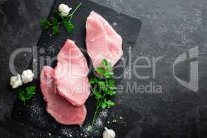 Raw meat, turkey steaks on black background, top view