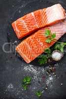 Raw salmon fish fillet on black background