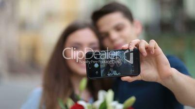 Loving couple on holiday making selfie on phone