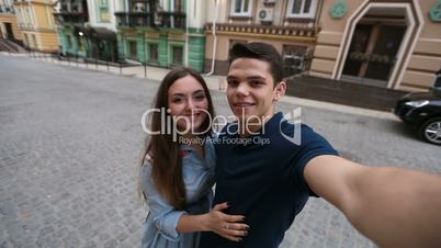 Cheerful young couple taking selfie on mobile phone