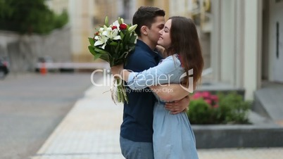 Young man giving bunch of flowers to girl on date