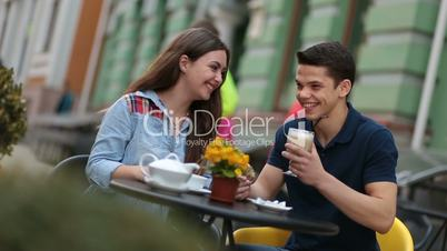 Young couple enjoying romantic date in street cafe