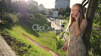 Cheerful blonde woman talking on phone outdoors