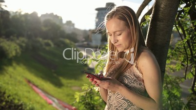 Joyful woman texting on smartphone in park