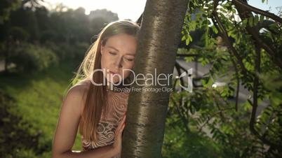 Portrait of pensive woman with head glued to tree.