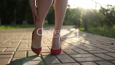 Woman in red high heels sprains foot on the street