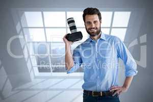 Composite image of portrait of confident photographer holding digital camera