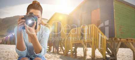 Composite image of young female photographer using digital camera