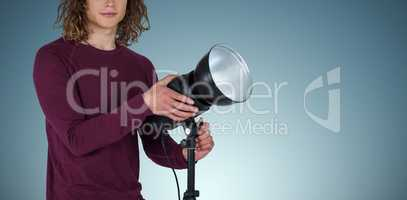 Composite image of portraot of young photographer holding focus light