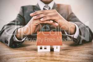 Composite image of businessman protecting house model with hands