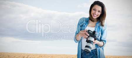 Composite image of portrait of young female photographer holding digital camera