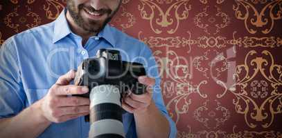 Composite image of smiling young male photographer looking at digital camera