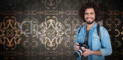 Composite image of portrait of happy photographer holding digital camera