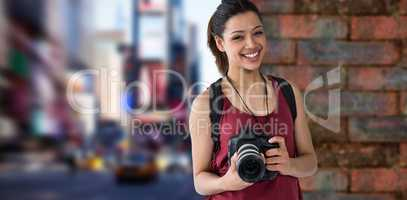 Composite image of portrait of happy female photographer with digital camera
