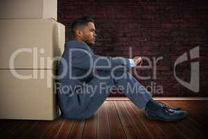 Composite image of businessman leaning on cardboard boxes against white background