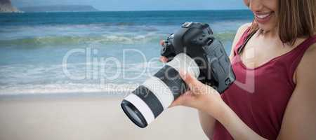 Composite image of happy young female photographer looking at digital camera