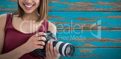 Composite image of portrait of smiling beautiful woman holding digital camera