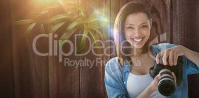 Composite image of portrait of smiling female photographer holding digital camera