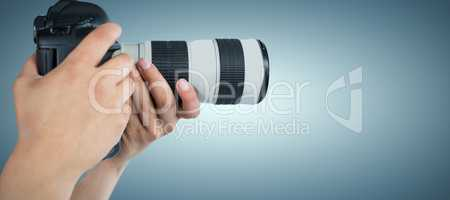 Composite image of cropped hands of photographer holding digital camera