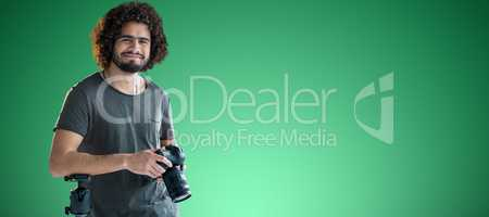 Composite image of portrait of happy young photographer holding digital camera