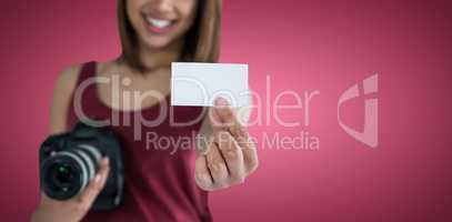 Composite image of happy woman showing identity card while holding camera