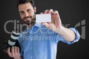 Composite image of happy man showing identity card while holding camera
