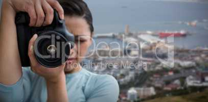 Composite image of young female photographer photographing through digital camera