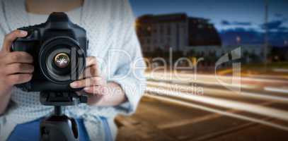 Composite image of mid section of woman holding digital camera