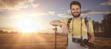 Composite image of portrait of confident young photographer holding digital camera