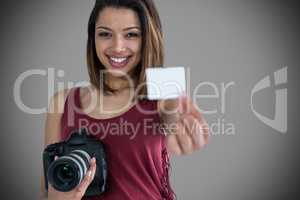 Composite image of portrait of happy woman showing identity card while holding camera