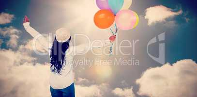 Composite image of full length rear view of carefree woman holding colorful balloons