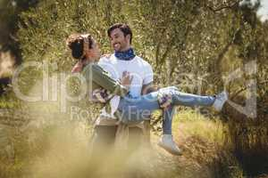Young man carrying girlfriend by trees at farm