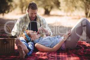 Cheerful man feeding strawberry to woman at farm