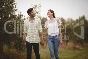 Young couple holding hands while walking on field at farm
