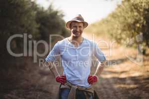 Smiling young man standing on dirt road at farm