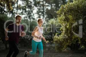 Determined young couple running on field at farm