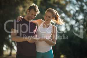 Happy young couple using mobile phone on sunny day
