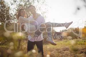 Happy young man carrying girlfriend while standing at olive farm
