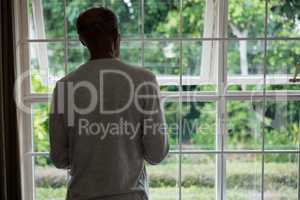 Rear view of senior man standing against windows